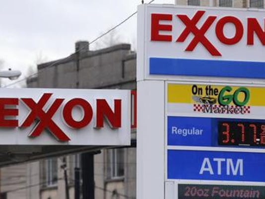 This April 29, 2014 photos shows Exxon signage at a mini-mart in Dormont, Pa. Exxon Mobil says net income fell 4 percent in the fourth quarter on lower production of oil and gas and weaker refining results.