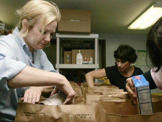 Sandy Murray, left, of Green Brook, Alice Stanko, center left, and Eleana Chambergo, out of frame, work to fill grocery bags of food distribution during the Lighthouse Ministries of Calvary Chapel in North Plainfield's weekly food drive last year. The bags are full of items pertaining to Thanksgiving, such as stuffing and cranberry sauce.