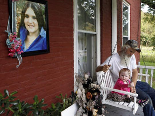 David Dodson sits with his granddaughter, Aubree Stykes, at his Ripley, Ohio home, near a memorial of his daughter Brittany Stykes, who was gunned down last year.