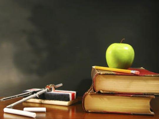 School books with apple on desk.