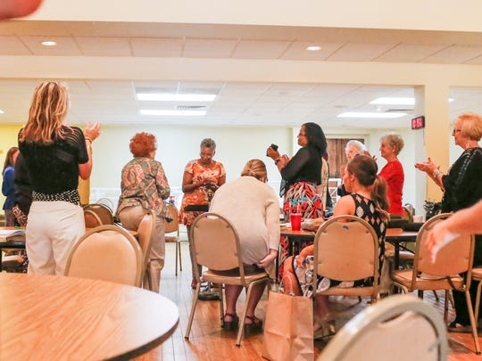 A group of women at a Bible study at First Baptist Church in Brookhaven applaud Regana Wells, center, after she shares her testimony of addiction and recovery on May 21.