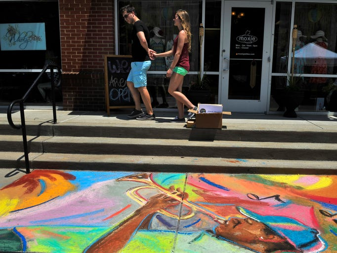 People walk by chalk art created by artist  James R. Threalkill at the Chalk it Up sidewalk chalk art competition  on Sunday, June 22, 2014, in Nashville.