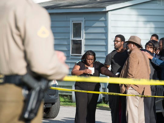 Onlookers gather outside of a house, where police say