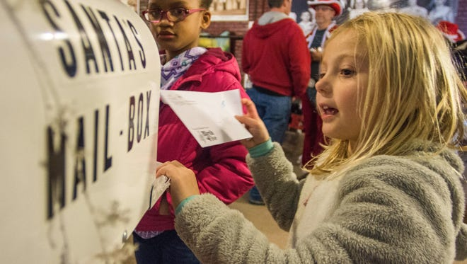 A girl puts a letter that she wrote to Santa Claus into a special mailbox for Santa during the 13th annual Old Fashioned Christmas Festival in the Depot District, Richmond, on Tuesday, Nov. 28, 2017.