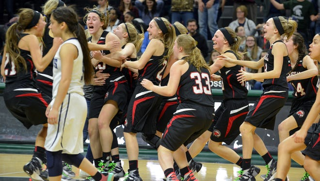 The Marshall Redhawks celebrate after winning the State Semilfinals, 43 - 42 over Bay City John Glenn Bobcats Friday night.