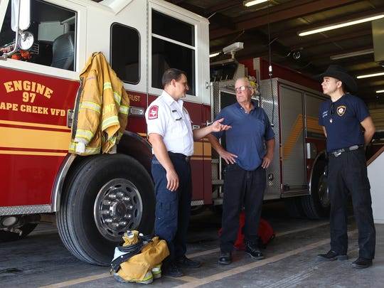 From left to right, Fire Chief Aaron Flint, Captain Joe Rutherford and Deputy Fire Chief Jose Rivera with the  Grape Creek Volunteer Fire Department discuss logistics for the coming weeks.