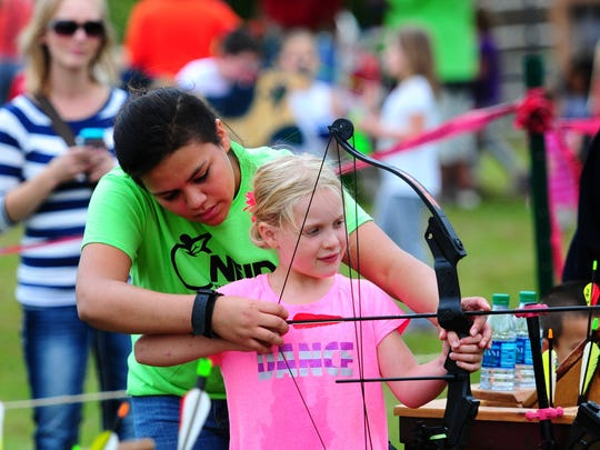 Kiara Skenandore helps Lainah Zuelzke line up a shot on the archery range during the Oneida Nation Big Apple Fest on Saturday at the Cultural Heritage grounds.