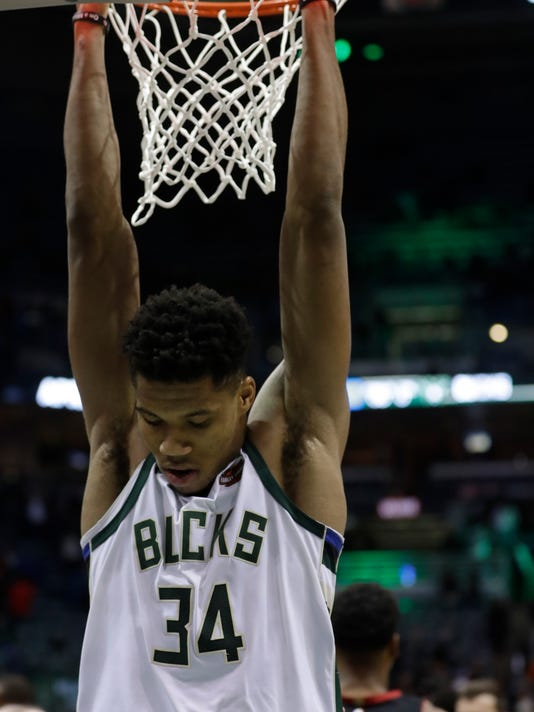 Milwaukee Bucks' Giannis Antetokounmpo hangs on the rim after an NBA basketball game against the Miami Heat Wednesday, Jan. 17, 2018, in Milwaukee. The Heat won 106-101. (AP Photo/Morry Gash)