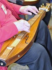 Elaine Johnson moves her hands over her dulcimer as she plays Christmas songs at the Boone County Library Florence branch Sunday, Dec. 13.