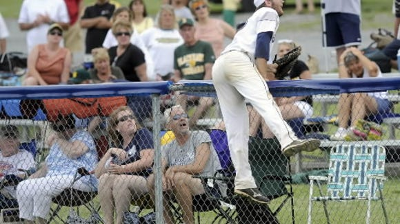 West York's Kaden Hepler leans over the fence while trying to catch a foul ball during Monday's semifinal.