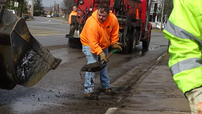 "Greg Farlee, with the Marion City Streets Department, takes advantage of a break in the rain Thursday to fill in potholes on Delaware Avenue at Walnut Street. It's a temporary fix, Farlee said. Scott Kurz, service and sanitation superintendent with the city, said the stretch of Delaware Avenue at Walnut Street is one of the main routes that has sustained the most damage over the winter. ""The freeze and thaw just keeps popping them up,"" he said. Kurz said that once the weather becomes warmer, the streets department will do more permanent work on the potholed roads around the city."