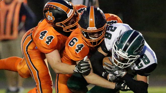 Plymouth's Jack Nytes (44) and Kody Hitsman (64) take down Kettle Moraine Lutheran's Jacob Byhardt Friday, September 15, 2017 in Plymouth, Wis.