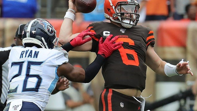 Cleveland Browns quarterback Baker Mayfield is pressured by Tennessee Titans' Logan Ryan.