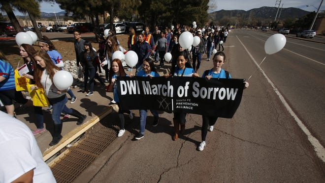 From the left, Destiny Jaramillo, 14, Juliana Martinez, 15, Samantha Sanchez, 14, Charlotte Bordegaray, 13, from Capshaw Middle School's Student Wellness Action Team, carry a sign during the DWI March of Sorrow/March of Hope, on Paseo de Peralta on their way back to the Capitol on Wednesday, February 17, 2016. The march was to honor 113 DWI deaths in 2015.