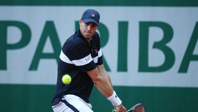 John Isner of the United States plays a backhand during the men's singles first round match against John Millman of Australia on day two of the 2016 French Open at Roland Garros on May 23.
