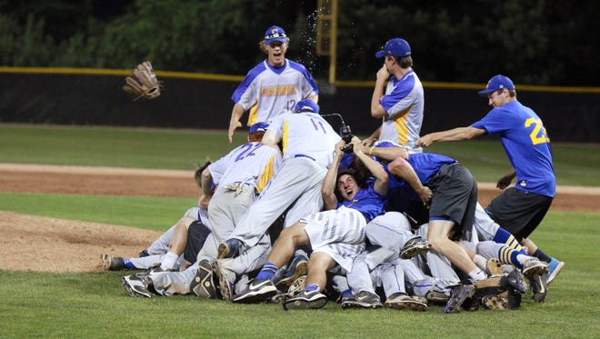 Carmel baseball players pile on each other after winning a sectional title Monday night over Westfield.