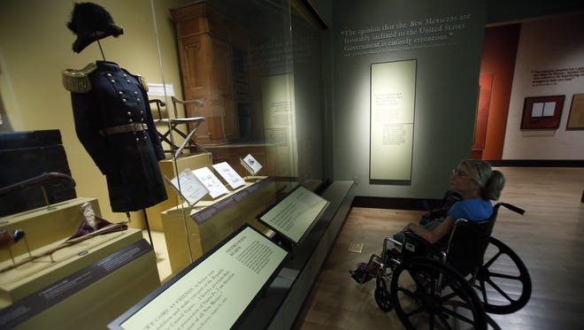 Jo Jaimeson, from Orem, UT, checks out the one of the Mexican-American War exhibits at The New Mexico History Museum on Friday, June 17, 2016. The Museum of New Mexico is no longer allowing New Mexicans free admission every Sunday. Now it's only the first Sunday a month.