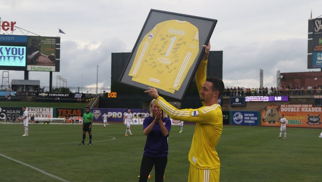 Louisville City FC goalkeeper Scott Goodwin, playing in his final match before enrolling at Harvard Medical School, raises a signed jersey given to him prior to LouCity's game against FC Montreal. LCFC won 2-0.