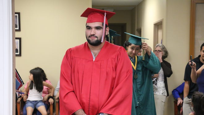 A 2015 summer graduating student from Desert Mirage High School receives his diploma. This summer's graduates received their diplomas this week.