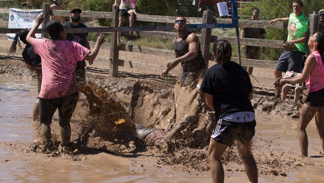 Jorge Hoyos dives after a ball and makes a giant muddy splash at the 7th annual Big Brothers Big Sisters Mudd Volleyball tournament on Saturday afternoon on Sept. 17, 2016.