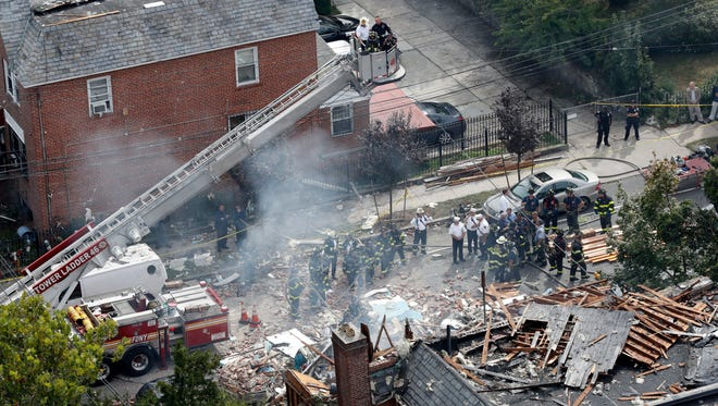 Emergency service personnel work at the scene of a house explosion, Tuesday, Sept. 27, 2016, in the Bronx borough of New York. Authorities say firefighters responding to a report of a gas leak Tuesday morning in the Bronx discovered what appeared to be a drug lab right before a two-story private house exploded. The Fire Department of New York says a firefighter has died in the house explosion. (AP Photo/Mary Altaffer)
