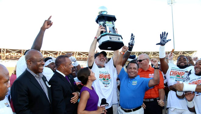 In this image provided by Old Dominion University,  ODU coach Bobby Wilder, center, and his team celebrate after their 24-20 win against Eastern Michigan in the Bahamas Bowl.