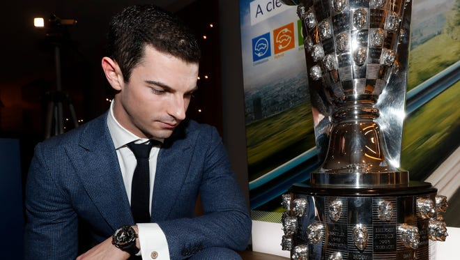 Alexander Rossi looks at his face on the Borg-Warner trophy Wednesday in Detroit.