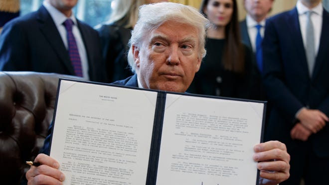 President Trump shows off his signature on an executive order about the Dakota Access pipeline.