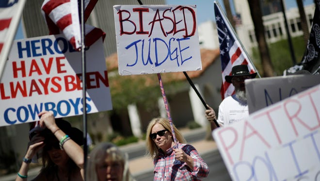 Marie Ries, center, marches with others in support of defendants on trial in federal court, Wednesday, April 12, 2017, in Las Vegas. A federal jury in Las Vegas heard closing arguments in the trial of six men accused of wielding weapons to stop federal agents from rounding up cattle near Nevada rancher Cliven Bundy's property in 2014. (AP Photo/John Locher)