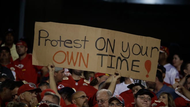 A Kansas City Chiefs fan holds a sign against the anthem protests during the first half of an NFL football game against the Washington Redskins.