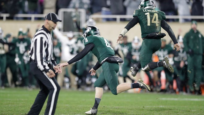 Michigan State kicker Matt Coghlin (4) and holder and quarterback Brian Lewerke react after Coghlin's game-winning field goal to defeat Penn State, 27-24, Saturday at Spartan Stadium.