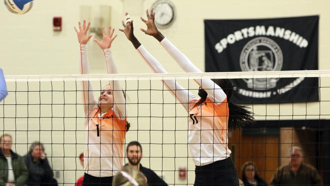 Laura Petterson (1) and Phekran Kong of Washington go up to block a shot at the net against Lincoln during Thursday's State AA Play-In game at Washington.