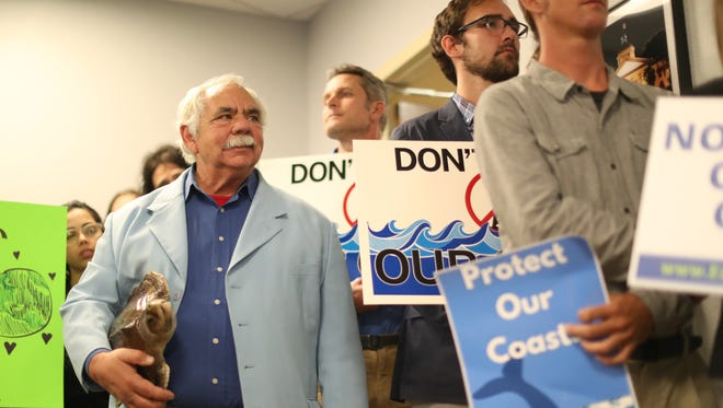 Jack Rudloe joins fellow protesters of the Bureau of Ocean Energy Management's discussion of new off shore oil drilling regulations during an open meeting at the Four Points Sheraton on Thursday,