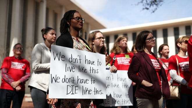 Brittney Clemons holds a sign with Moms Demand Action, a group lobbying for new gun control measures in the face of the mass of school shootings that have plagued the county, gather at the Capitol on Thursday, Feb. 15, 2018.