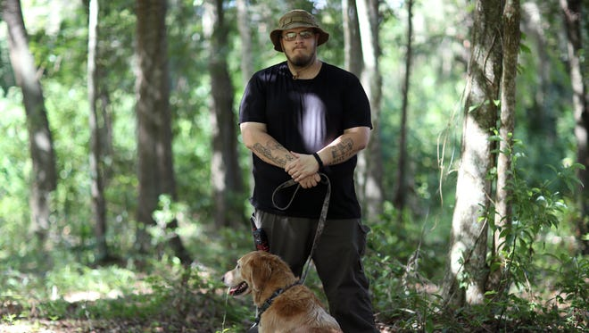 Jordan Jereb, a leader of a local Tallahassee cell of the Republic of Florida militia, a group backing the separation of races and a Florida secession from the United States, stands with the ROF flag in the woods near his home on Thursday, Aug. 17, 2017.