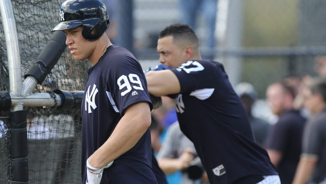 Aaron Judge and Giancarlo Stanton wait to hit in the batting cage.