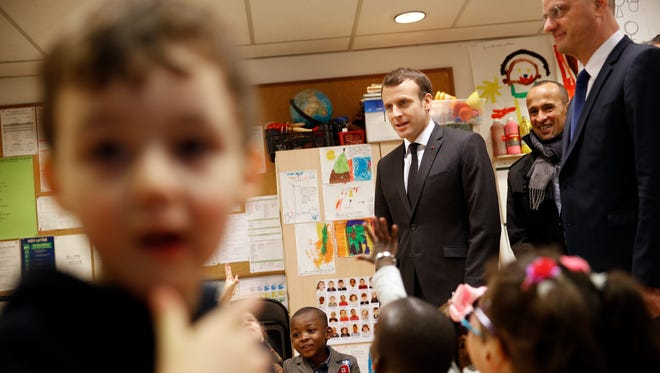 French President Emmanuel Macron, center, and French Education Minister Jean-Michel Blanquer, right, speak with pre-school children as the visit the Emelie pre-school in Paris, on March 27, 2018.