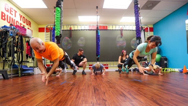 Guy DiTommaso, left, works out with Charinee Bangthamai, of Cape Coral, and other classmates in the Astro-Durance class. They were doing clap pushups.Last July, Patty Cummings launched her bungee workout system brand, Astro-Durance. She had 1,500 square feet of strip mall space, two full-time employees and was dealing in Florida. Less than a year later, she has leased 5,000 square feet of space, hired 13 more full-time employees and shopped her product to 33 states plus Australia, Turkey and Costa Rica. She's looking to further her brand, appearing on national podcasts and a fitness reality show in 2019. Cummings just might be onto the next national fitness craze.