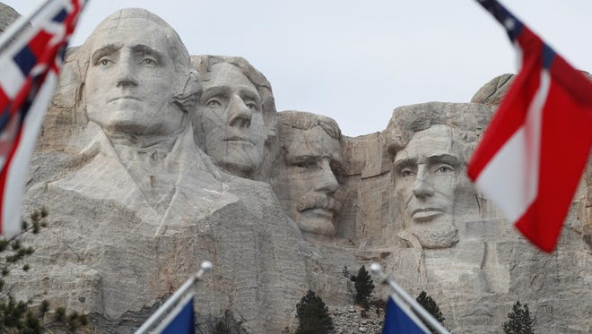 Flags frame the presidents on the Mount Rushmore monument Friday, Dec. 9, 2016, near Keystone, S.D.The Arctic cold front has sent daytimes highs barely above zero degrees for the week in the mid-plains. (AP Photo/David Zalubowski)