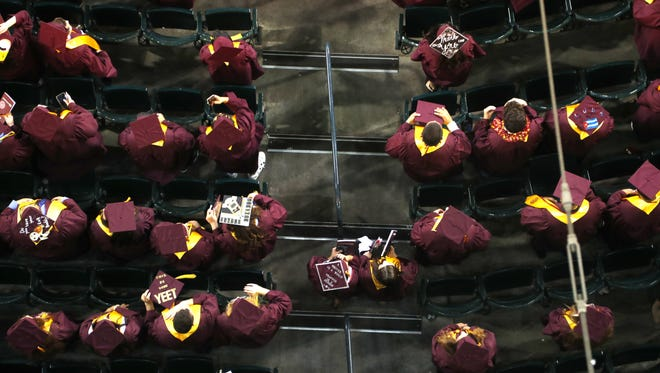 ASU graduates stand for the national anthem during Arizona State University's undergraduate commencement ceremony at Chase Field in Phoenix, Ariz. on May 7, 2018.