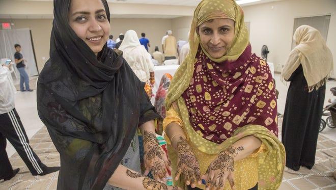 Farzana Salahudeen (left) and Julaiha Ariff show off henna during Ramadan at Foothills Christian Church in Glendale.