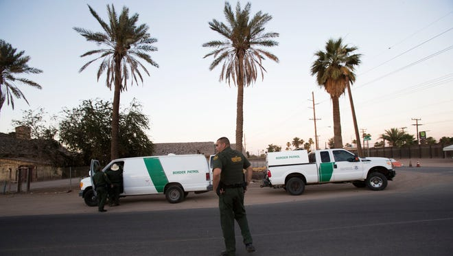 Customs and Border Protection agents prepare to move undocumented immigrants after having detained them once they entered the U.S. at the Calexico/Mexicali international border wall on June 19, 2018.