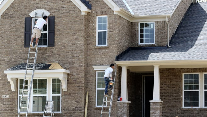 Painters work on a new house at Sycamore Grove by Drees Homes on Kenwood Road.