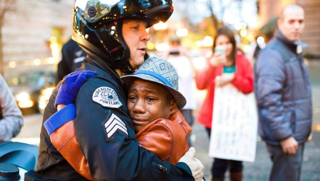 In this Tuesday, Nov. 25, 2014 photo provided by Johnny Nguyen, Portland police Sgt. Bret Barnum, left, and Devonte Hart, 12, hug at a rally in Portland, Ore., where people had gathered in support of the protests in Ferguson, Mo.