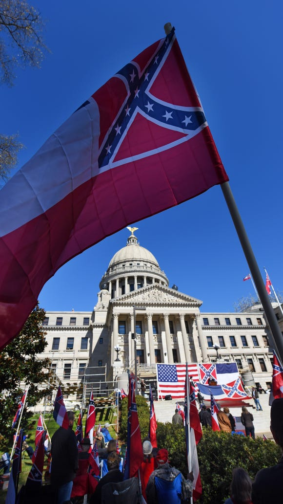Supporters of keeping Mississippi's state flag wave it last week during a rally at the state Capitol in Jackson.