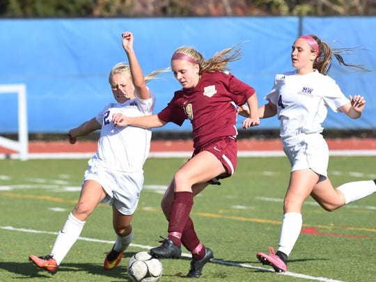 Arlington's Molly Feighan, center, tries to keep the