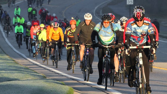 Cyclists travel through a shaft of early morning sunlight Sunday on Brighton Road during the Tour de Livingston bicycle tour. About 600 riders took part in the ride, organized by the Howell Rotary Club to benefit the Livingston County United Way.
