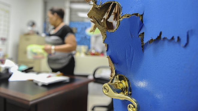 The damaged door of Assistant Principal Elizabeth Hanzsek's office is shown as she cleans her office after a break-in at FB Leon Guerrero Middle School in Yigo in November 2014. Rick Cruz/Pacific Daily News/rmcruz@guampdn.com