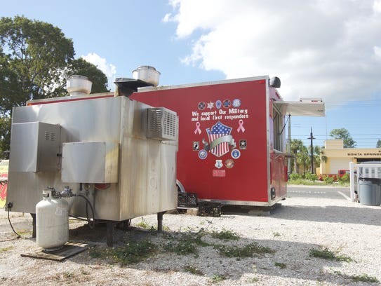 A giant smoker sits behind Smokin R's BBQ trailer at