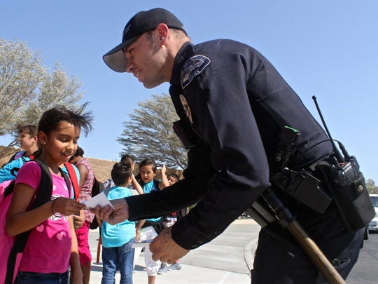 """Desert Hot Springs police officer Cory Carranza """"tickets"""" a student for good behavior at Two Bunch Elementary School on Aug. 18, 2015. A new program rewards students with tickets for free 7-Eleven Slurpees."""